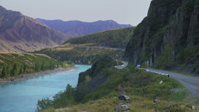 Wide Siberian Mountain River Landscape With Mountain Road And Car Passing. Blue Water Stream Slowly Flowing Through The Mountain Canyon In Altai Russia On A stock footage