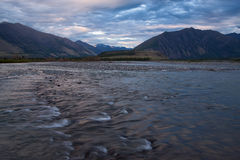 Wide and soft mountain river with rapids. Royalty Free Stock Photography