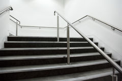 Wide staircase with chrome handrails. And gray steps, white walls stock image