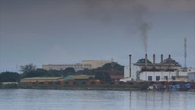 View of a mining factory, Conakry coast, Guinea. Wide, steady clear shot of an iron ore refinery plant, offshore, buildings, Conakry, bushy land trees, dark stock footage