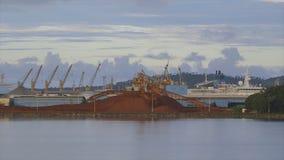 Bauxite alumina mine site, Kaloum , Conakry, Guinea. Wide steady shot, Conakry, calm evening, quiet grey water, dark light clouds bauxite mine site, offshore stock footage