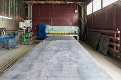 Wide steel sheet in front of old guillotine scissors. Sheet metal processing shop Stock Image