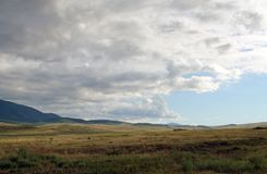 Wide steppe with yellow grass under a blue sky with white clouds Sayan mountains Siberia Russia. Beautiful hill Royalty Free Stock Images