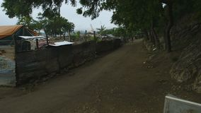 Dusty road at Moresby port, Papua New Guinea. Wide still shot of a clear dusty road with trees , passing close to a sheet-metal fence of a slum dwelling, Moresby stock footage