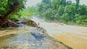 Wide stormy mountain river swirls by high smooth rocky bank stock footage
