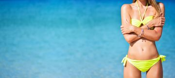 Wide summer banner with beautiful fit young woman in yellow bikini at the beach. Girl in swimsuit and sunglasses royalty free stock image