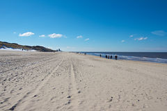 Wide Sylt Beach. Hikers walking along a wide Nort Sea beach towards Westerland city on Sylt island, Germany Royalty Free Stock Photography
