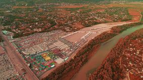 Aerial shot of highway and cars, which are moving fast along the bridge near commercial enterprises. 4K. Wide tranquil river divides rural area, enclosed by stock footage