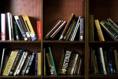 A wide variety of books on wooden shelves inside a library. Royalty Free Stock Photo