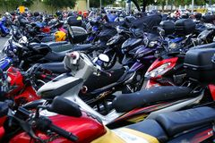 A wide variety of motorcycles in a parking lot outside a mall. Royalty Free Stock Photo