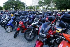A wide variety of motorcycles in a parking lot outside a mall. Royalty Free Stock Photos