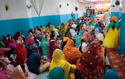 Indian sikh women seen inside their temple during Baisakhi celebration in Mallorca wide view. Wide view from back in the temple on Indian Sikh women and their Stock Photo