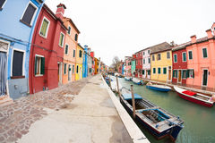 Wide view on colorful houses from a secondary street in Burano island during a cloudy winter day Royalty Free Stock Images