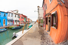 Wide view on colorful houses from a secondary street in Burano island during a cloudy winter day Stock Photo