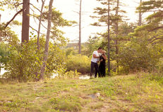 Wide view of couple by the lake with dogs Stock Images