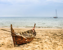 Old beached fishing Boat - Asian Style. Wide view of a desert beach in Thailand (Ko Lanta) with an abandoned boat with a dramatic atmosphere Stock Photos