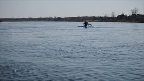 Wide view of Disabled sportsman rowing on the river in a canoe. Rowing, canoeing, paddling. Training. Kayaking. Wide view Disabled sportsman rowing on the river stock footage