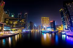 Wide View Of The Dubai Marina At Night. A wide view of the Dubai Marina at night, with many buildings and bright lights visible on either side stock photo