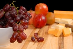 Wide view of fruit and cheese on cutting board. Wide view of delicious fruit and cheese on cutting board containing grapes, apples, pears, nectarines as well as Royalty Free Stock Photography
