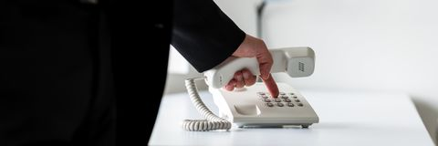 Wide view image of businessman dialing telephone number stock photography