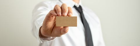 Businessman holding blank wooden peg towards the camera. Wide view image of businessman holding blank wooden peg towards the camera. Over grey background stock images