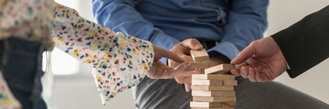 Free Wide View Image Of Three Business People Making A Tower Of Wooden Pegs Royalty Free Stock Photos - 140361888