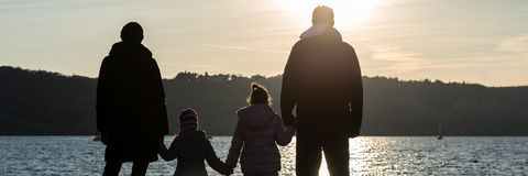 Wide view image of silhouette of a family with two kids by the sea royalty free stock photo