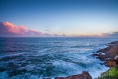 Wide View of Sea Waving on the Rocks during Daytime Stock Photography
