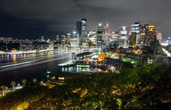 Wide view of Sydney CBD cityscape at night with light trails from ferry traffic in Circular Quay. Wide-angle view of the Sydney central business district royalty free stock photography