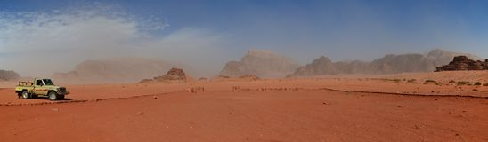 Wide vista of sand and rocky outcrops, Wadi Rum, Jordan. Driving through the desert, in Wadi Rum, Jordan, towards one of the magnificent rocky outcrops which royalty free stock photo