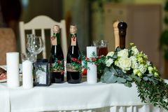 The wide white candle and two green bottles with red wine decora Royalty Free Stock Photo