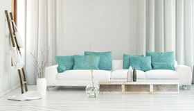 Wide white sofa in front of flowing curtains. Wide white sofa decorated by turquoise colored pillows in between flowing curtains and large glass vase with Royalty Free Stock Images
