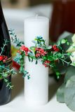 The wide white wedding candle decorated by a red flowers and gre. Enery Stock Photography