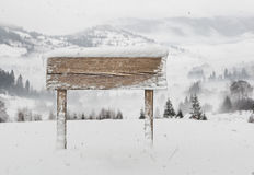 Wide wooden signpost with snow and mountains Stock Photo