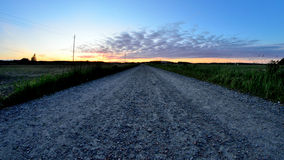 Wideangle landscape straight gravel road. Countryside landscape of gravel road and sunset, some clouds on the sky and colours. Picture taken with fisheye lens Stock Photos