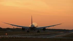 Widebody tweelingmotorvliegtuig die in de vroege ochtend landen stock videobeelden