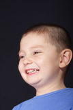 Widely smiling boy. Boy in blue shirt smiling videly head and shoulders photo Stock Photo