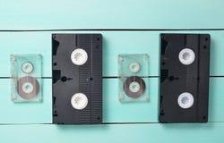 Wideo kasety i audio kasety na turkusowym drewnianym stole Retro wideo i audio technologia Fotografia Stock