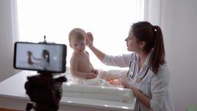 Wideo nauczanie, blogger kobiety rodzinna lekarka uczy abonentów egzamininować dziecka w domu i nagrywający ogólnospołecznych śro zbiory
