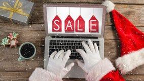 Wideo skład z śniegiem nad biurkiem z Santa ręką na laptopie zbiory