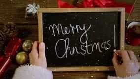 Wideo skład z spada śniegiem nad biurkiem z Santa mienia blackboard z wesoło bożymi narodzeniami zdjęcie wideo