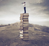 Wider horizons. Businessman standing on a stack of books on a hill and using a telescope Royalty Free Stock Photos