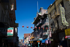 Wider view of an historic street in Chinatown, San Francisco, with red lanterns hanging across. The diverse immigrant populations of America are well Stock Photos