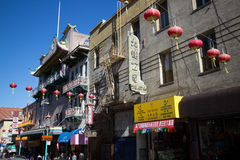 Wider view of red Chinese lanterns hanging over a street in Chinatown, San Francisco. Note that English is the minority language on the various local shop Stock Image