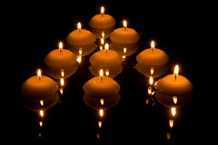 Widergespiegelte brennende Kerzen, die auf Wasser schwimmen Stockbild