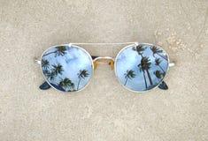 Widergespiegelte Sonnenbrille nah oben auf dem Strandsand mit Palmereflexion stockfotos