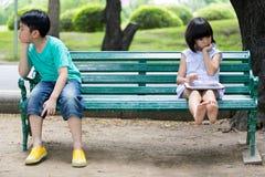 Widersprechen Sie zwischen dem asiatischen Bruder und der Schwester, die auf einem woode sitzen Stockbilder