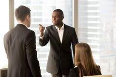 Widersprechen Sie zwischen männlichen Schwarzweiss-Büroangestellten am workplac Stockfotografie