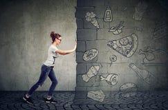 Widerstehende Versuchung der motivierten Frau des Essens des schnellen Fußes und des Wählens der besseren Diät Lizenzfreies Stockfoto