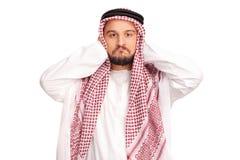 Widerstrebender männlicher Araber, der seine Ohren bedeckt Stockbild
